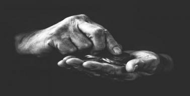 Mãos contando moedas (em foto em preto e branco)