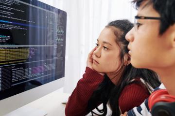 Uma garota e um garoto adolescentes olhando códigos de programação em uma tela de computador