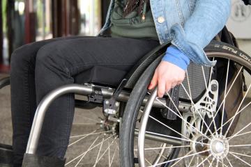 Close de cadeira de rodas, mostrando a mão de uma mulher a conduzindo