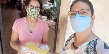 Uma mulher, de máscara, entrega um pacote para uma senhora, também de máscara, à porta de uma casa