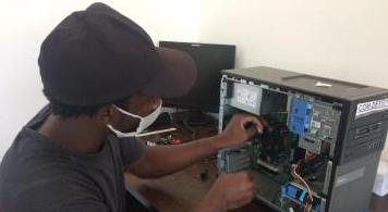Jovem negro, de máscara e boné, de costas, consertando CPU de computador desktop