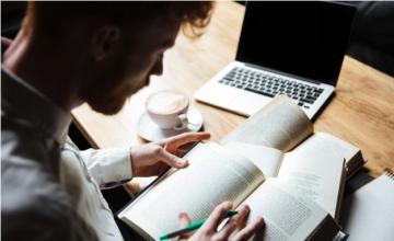 Estudante com livro, computador e uma xícara de café