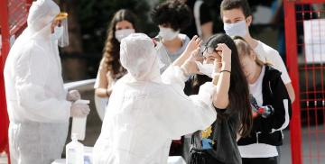 Pessoas com EPI vestem máscara e oferecem álcool em gel para adolescentes em fila