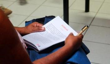Close de pessoa fazendo o curso, em que mostra uma apostila no colo e as mãos segurando