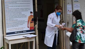 Profissional do Hucam, com máscara N95 e termômetro em uma das mãos, aplica álcool 70% nas mãos de paciente à entrada do hospital