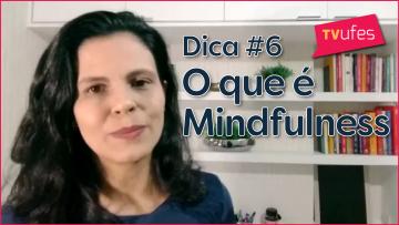 """Imagem de uma mulher em um local que tem ao fundo uma prateleira branca com livros. À frente está escrito o título do episódio, """"Dica #6 - o que é mindfullness"""""""