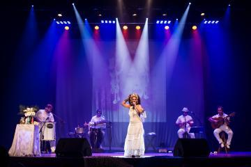 Cantora Monique Rocha e banda, no palco, durante show no Teatro Universitário da Ufes