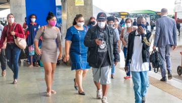 Pessoas na calçada, de máscara, de várias idades, raças, gêneros
