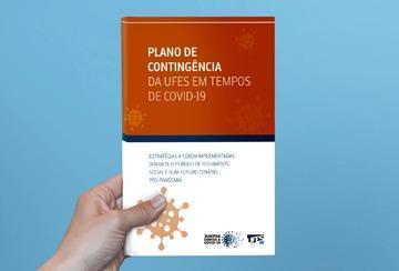Mão segura documento inicial do Plano de Contingência da Ufes em tempos de COVID-19
