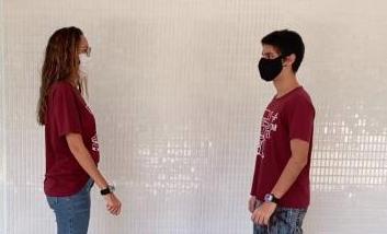 Mulher e homem, de máscaras, usando a pulseira anti-covid