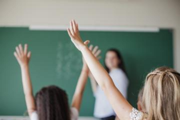 Em uma sala de aula, com a professora e um quadro negro ao fundo, duas estudantes levantam as mãos.