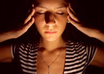 Mulher jovem com as mãos na cabeça e os olhos fechados